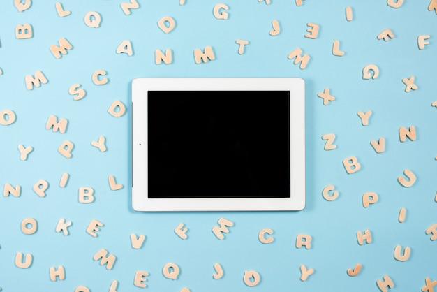 Digital-tablette mit der schwarzen bildschirmanzeige umgeben mit hölzernen buchstaben auf blauem hintergrund