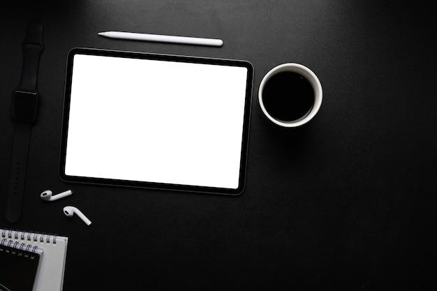 Digital-tablette mit leerem bildschirm, stylus-stift, drahtlosem kopfhörer und kaffeetasse auf dunklem tisch.