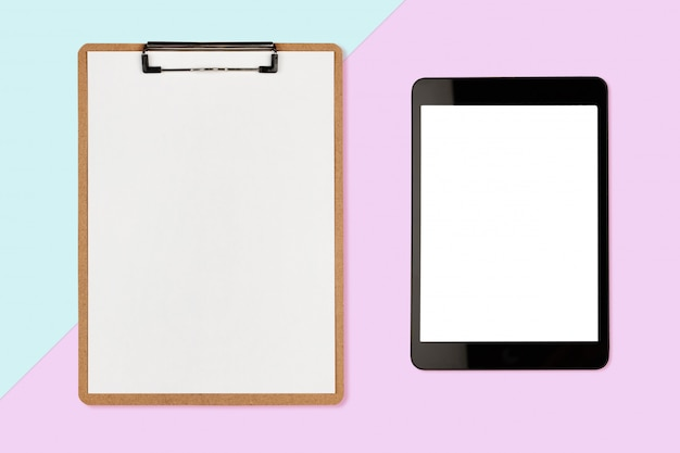 Digital-tablette mit leerem bildschirm und klemmbrett auf pastellfarbhintergrund