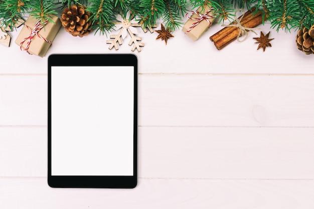 Digital-tablette mit rustikalem weihnachtshölzernen hintergrunddekorationen für app-darstellung. draufsicht mit copyspace. getönten