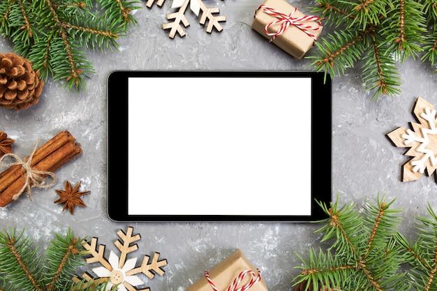 Digital-tablette mit rustikalen weihnachtsgrauen zementhintergrunddekorationen für app-darstellung. draufsicht mit copyspace