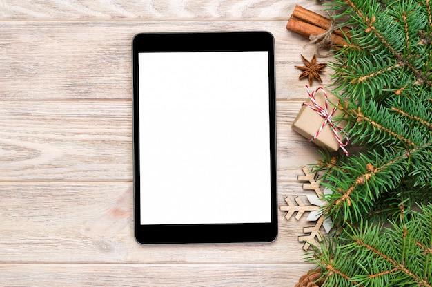 Digital-tablette mit rustikalen weihnachtshölzernen hintergrunddekorationen für app-darstellung. draufsicht mit copyspace