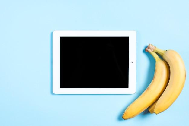 Digital-tablette mit schwarzem bildschirm und banane auf blauem hintergrund