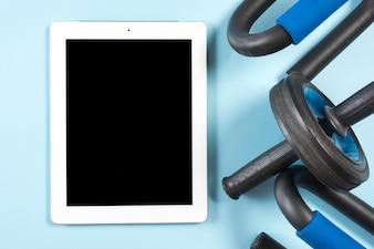 Digital-Tablette mit schwarzen Anzeige- und Turnhallenausrüstungen auf blauem Hintergrund
