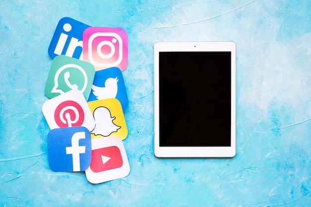 Digital-tablette nahe gerundete ikonen von social media gesetzt, die auf papier gedruckt wurden, schnitt heraus