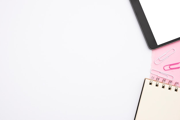 Digital-tablette und gewundenes tagebuch mit papierklammer über weißem hintergrund