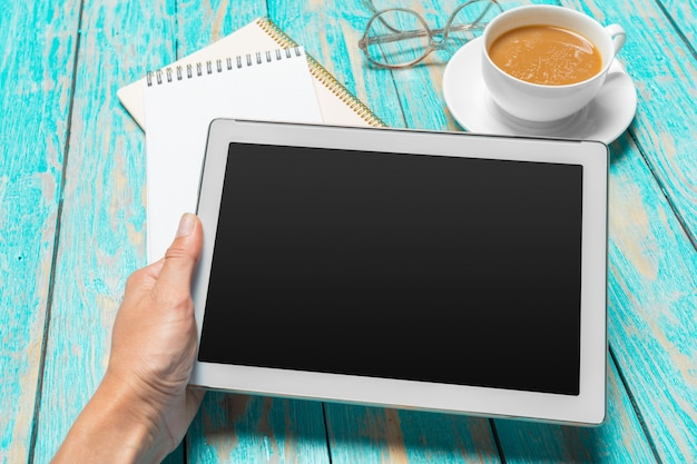 Digital-tablette und kaffeetasse auf holztisch