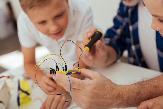 Digitale entwicklung. elektronisches mikroschema mit drähten in den händen eines netten positiven mannes