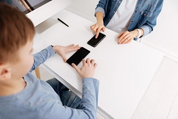 Digitale geräte. draufsicht der modernen smartphones, die auf dem tisch liegen, mit positiv glücklicher mutter und sohn, die sie betrachten