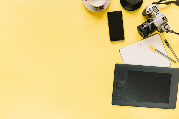 Digitale grafiktablette; kamera und handy mit briefpapier auf gelbem hintergrund