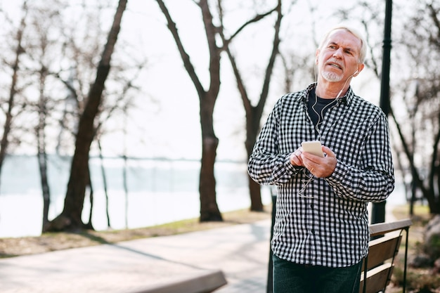 Digitale musik. erfreulicher älterer mann, der sich auf die bank stützt und musik hört