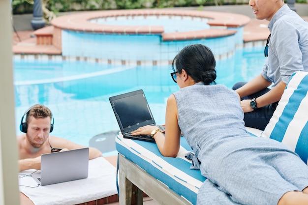 Digitale nomaden, die am schwimmbad arbeiten