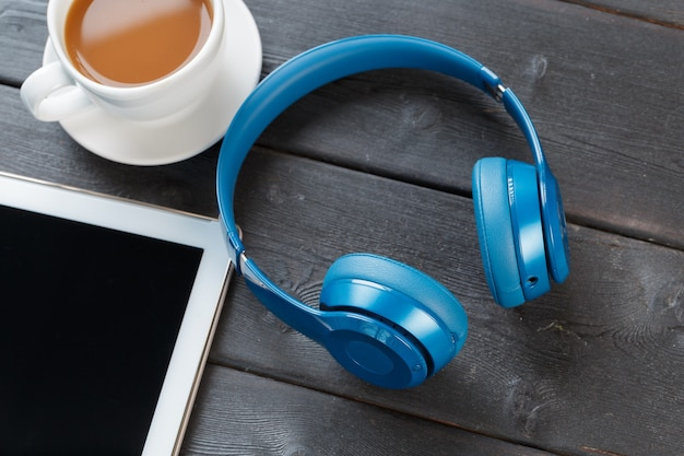 Digitale tablette auf holztisch im café mit tasse kaffee