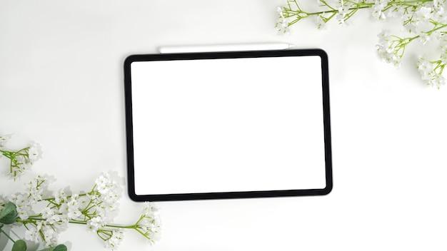 Digitale tablette auf mittelrahmen mit blumenstrauß, leere bildschirmanzeige für geschenk.