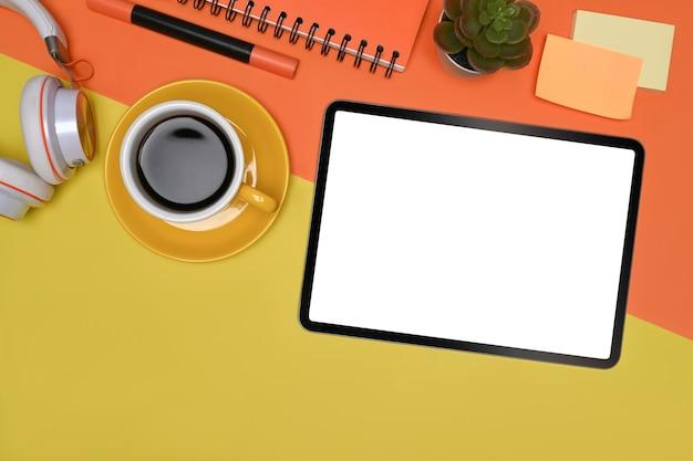 Digitale tablette der draufsicht, kaffeetasse und klebrige anmerkungen auf buntem hintergrund.