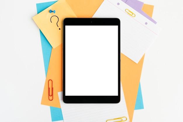 Digitale tablette des leeren bildschirms auf buntem papier und papierklammern