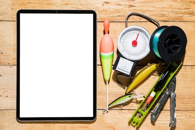 Digitale tablette des leeren bildschirms mit angelausrüstung auf hölzernem schreibtisch