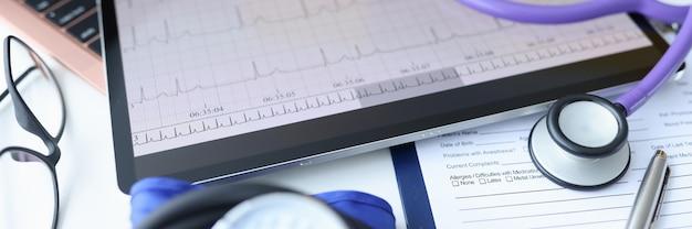 Digitale tablette mit elektrokardiogramm, die auf dem schreibtisch des arztes liegt, nahaufnahme der ekg-diagnose des rhythmus