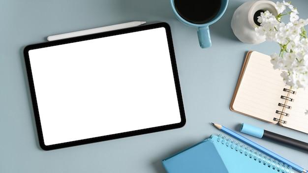 Digitale tablette mit weißem bildschirm, kaffeetasse, notizbuch und stiften auf blauem pastellhintergrund.