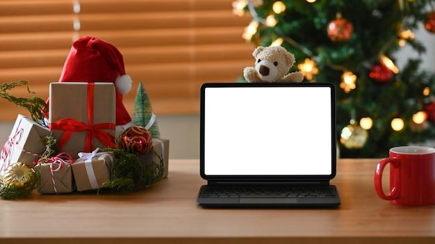 Digitale tablette, tasse kaffee und weihnachtsgeschenke auf holztisch.