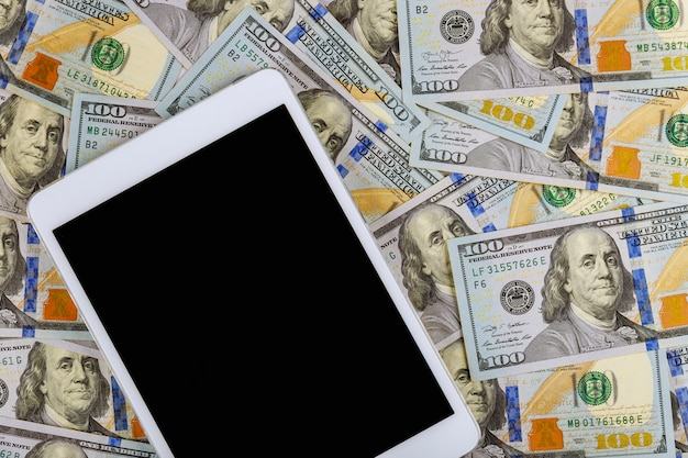 Digitale tablette und bargeld der technologie über amerikanischem dollarkonzeptgeschäft des marmorhintergrundes