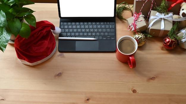 Digitale tablette, weihnachtsmütze und weihnachtsgeschenkboxen auf holztisch.