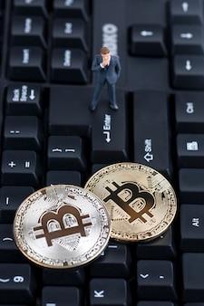 Digitale währung, bitcoin mit miniaturgeschäftsmann auf tastatur