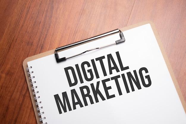 Digitaler marketingtext auf weißem papier auf dem holztisch
