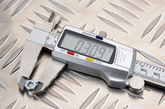 Digitaler messschieber aus metall auf rutschfester aluminium-metallplatte mit rautenmuster