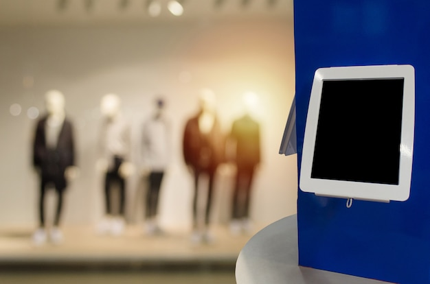 Digitaler monitor oder tablette des leeren bildschirms auf zähler mit unscharfem bild des populären mannmodekleidungs-shopschaukastens