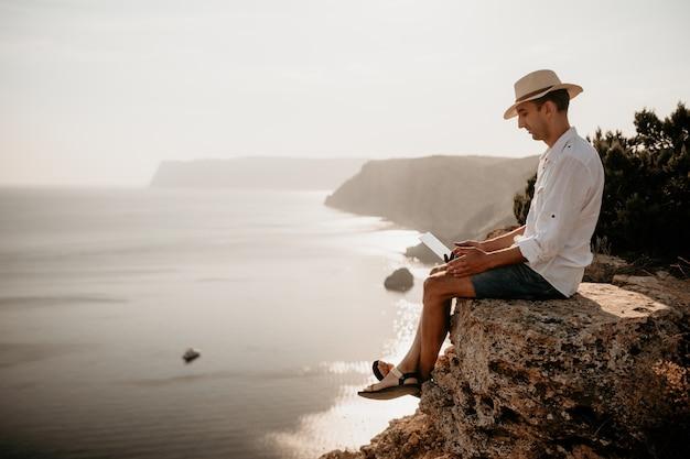 Digitaler nomadenmann mit hut ein geschäftsmann mit laptop sitzt bei sonnenuntergang auf den felsen am meer