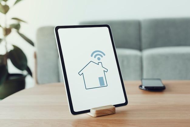 Digitaler tablet-bildschirm mit smart-home-controller auf einem holztisch