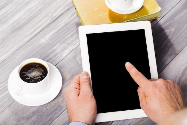 Digitaler tablet-computer mit isoliertem bildschirm in männlichen händen über café-hintergrund - tisch,