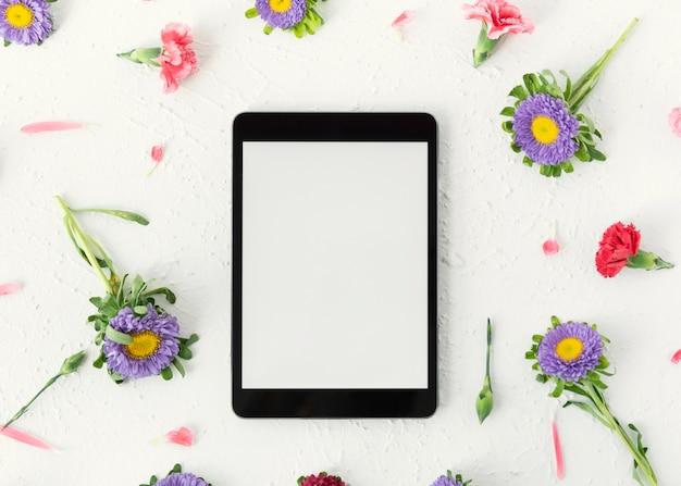 Digitaler tablettenkopienraum der draufsicht umgeben durch blumen