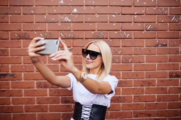 Digitaler verbund der tausendjährigen frau, die selfie gegen rote backsteinmauer nimmt