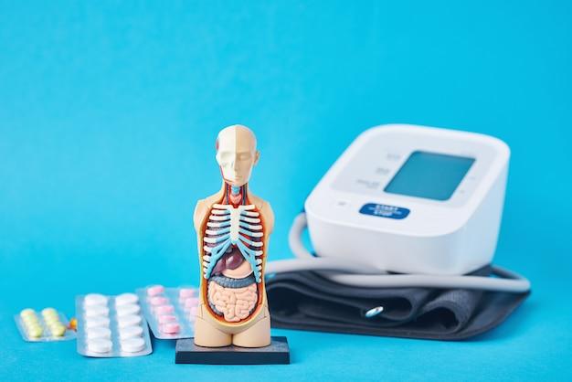 Digitales blutdruckmessgerät, anatomische puppenmann-schaufensterpuppe und medizinische pillen auf blauem hintergrund. gesundheits- und medizinkonzept