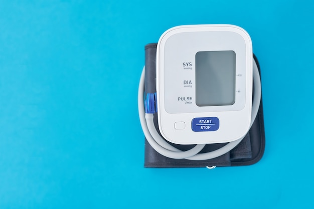 Digitales blutdruckmessgerät auf blau, nahaufnahme. helathcare und medizinisches konzept