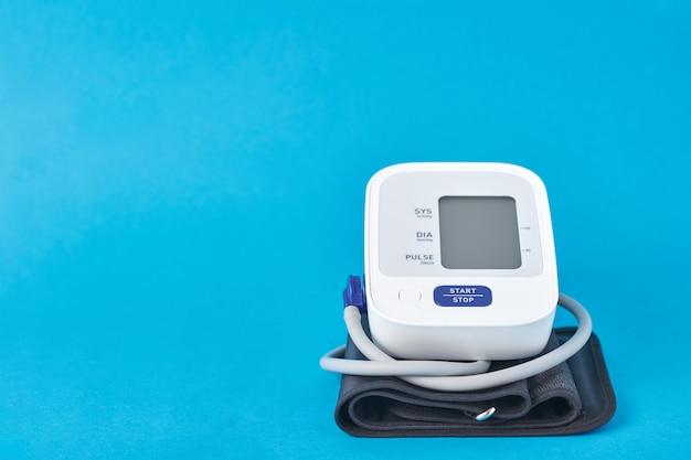 Digitales blutdruckmessgerät auf blau, nahaufnahme. helathcare- und medizinkonzept