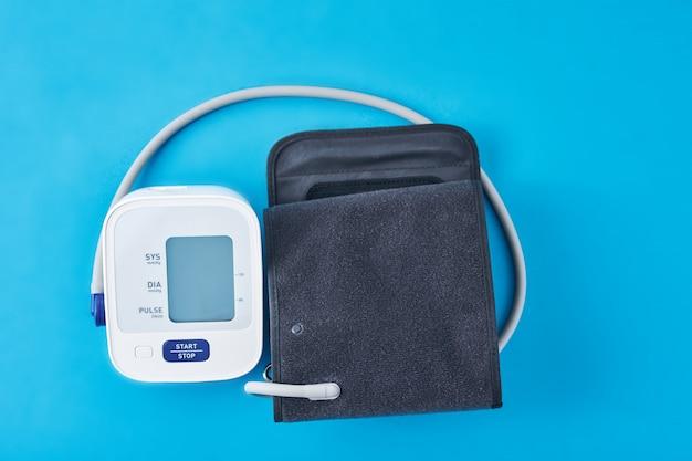 Digitales blutdruckmessgerät auf blauem hintergrund, nahaufnahme. helathcare und medizinisches konzept