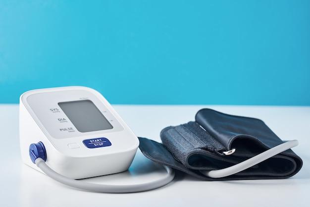 Digitales blutdruckmessgerät auf blauem hintergrund