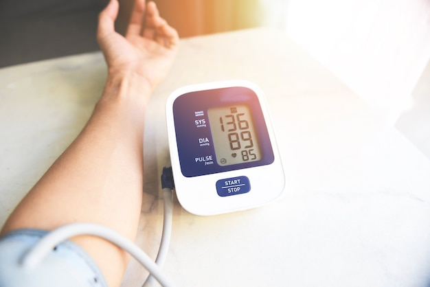 Digitales blutdruckmessgerät auf holztisch, medizinisches elektronisches tonometer zur blutdruckkontrolle