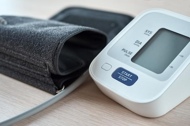 Digitales blutdruckmessgerät auf tisch, nahaufnahme.