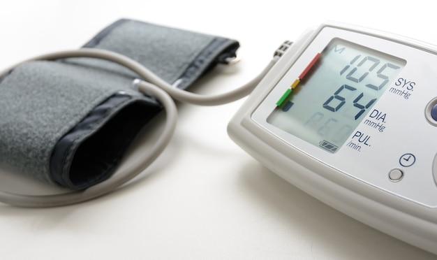 Digitales blutdruckmessgerät auf weißem tisch