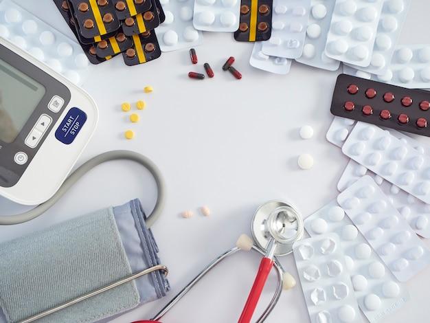 Digitales blutdruckmessgerät mit medizinischem stethoskop und medikamenten auf weißem tisch. gesundheits- und medizinkonzept