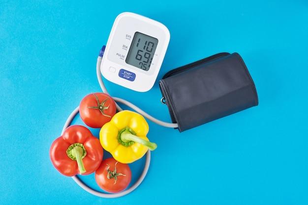 Digitales blutdruckmessgerät und frisches gemüse auf blauem hintergrund. gesundheitskonzept