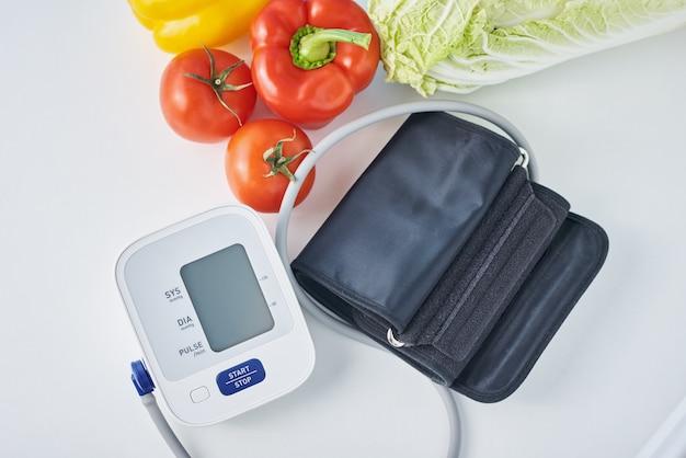 Digitales blutdruckmessgerät und frisches gemüse auf dem tisch. gesundheitskonzept