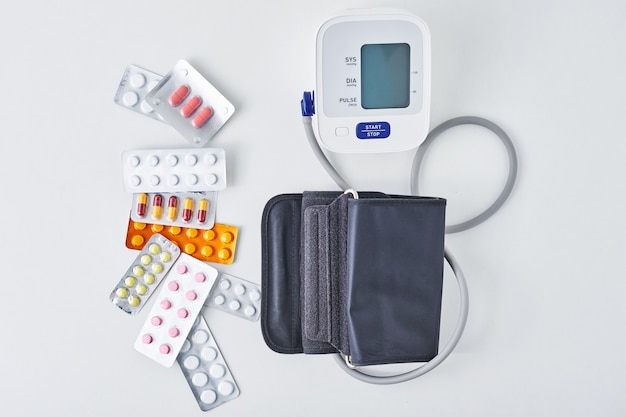 Digitales blutdruckmessgerät und medizinische pillen auf weißem tisch. gesundheits- und medizinkonzept