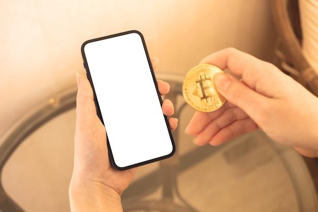 Digitales geldmodell, zahlung mit bitcoin-konzept, frau mit handy und goldener münze