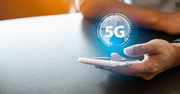 Digitales hologramm des netzes 5g und internet von drahtlosen systemen des netzes 5g nahaufnahme der männliche hand schreibenden mitteilung auf mobilem smartphone.