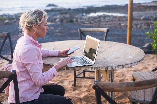 Digitales nomadenkonzept mit blonder, freier, schöner, kaukasischer frau mittleren alters, die am laptop arbeitet und auch ein mobiltelefon verwendet, das auf einem holztisch in der nähe des ozeans sitzt - freiberuflich frei, um überall zu arbeiten